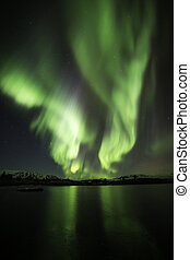 Auroras in Iceland - Northern lights blazing over lake...