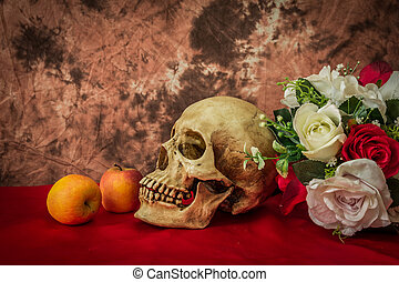 Still life with a human skull with apples and red and white...