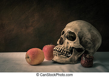 Still life with skull man with apples on a white floor.