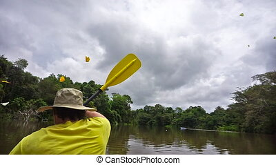 Kayaking in the Amazon - Young man kayaking in the Amazon...