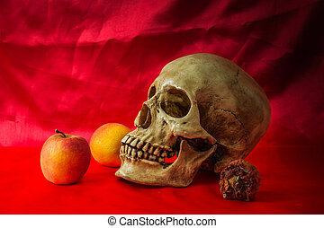 Still life with skull human with apples on a red floor