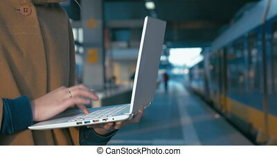 Girl working with laptop at the railway station - Close-up...