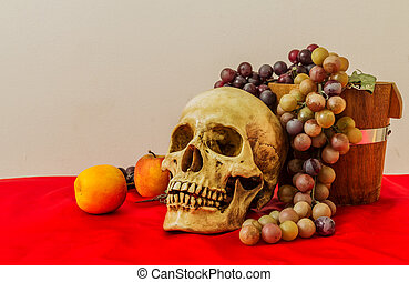 Still life with a human skull with fake apples and grapes on...
