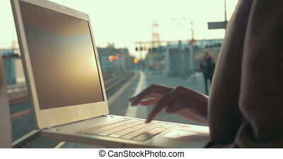 Woman using laptop at the station platform - Close-up shot...