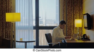Young businessman busy with work in hotel room