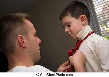 Father and Son - A young dad helps his son get ready by...
