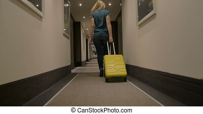 Woman with suitcase walking in hotel corridor