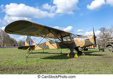 Old military airplane on green grass with blue sky and white...