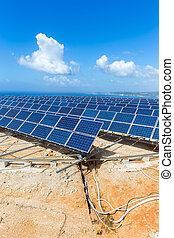 Rows of solar panels near sea with blue sky - Many rows of...