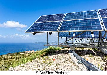 Solar panels near blue sea and monastry - Many blue solar...