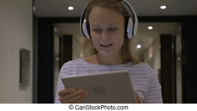 Timelapse of girl listening to music with tablet PC -...