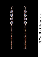 gold earrings with jewels on the black background