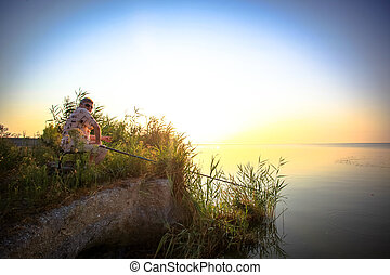 Young man fishing at misty sunrise in the morning HD...