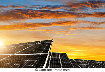 Solar energy panels against sunset sky