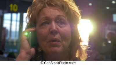 Senior woman having a vivid phone talk at airport - Close-up...