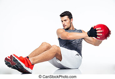 Fitness man working out with fitness ball isolated on a...