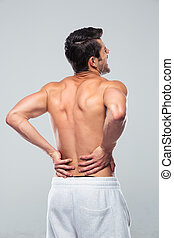 Portrait of a man standing with back pain over gray...