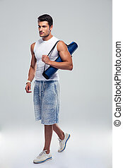 Fitness man walking with yoga mat
