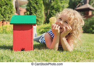 Little blonde girl  lying on the grass with house toy