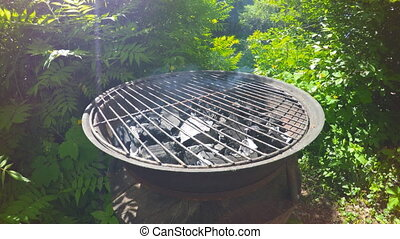 Open charcoal grill. - Open charcoal grill with burning...