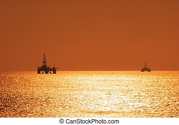 Two offshore oil rigs during sunset in Caspian se - Two...