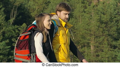 Capture a Moment - Side view of couple hiking in the...