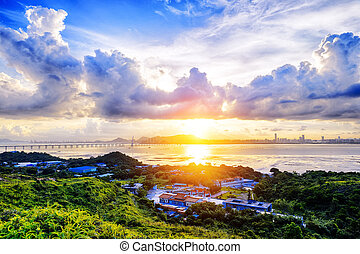 Village with beautiful sunset over hong kong  coastline.