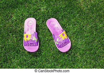 Blue sandals/flip flops on the green grass