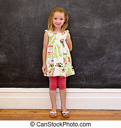 Beautiful little girl standing against blackboard at home -...
