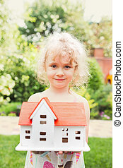 Portrait of little girl standing on grass with wooden model of house in hands,  summer outdoor, new home concept