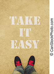 Take it easy text is painted on the ground in front of the...