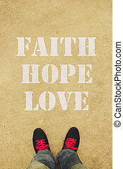 Faith hope love text is painted on the ground in front of...