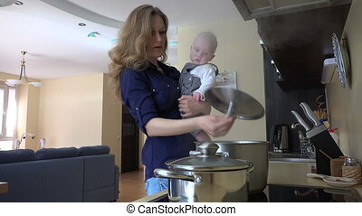 mom with baby kitchen - young mother with child in arms mix...