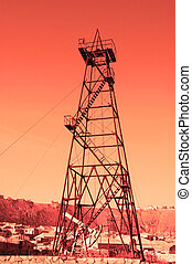 "Oil derrick with ""donkey\"" pump during sunset"