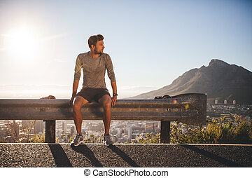 Man taking a break after morning run - Male runner sitting...