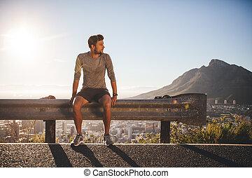 Man taking a break after morning run - Male runner sitting...