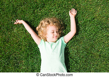 Dreaming adorable girl lying on grass, top view