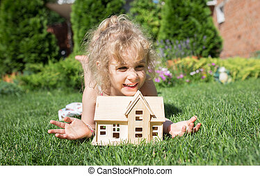 Portrait of little girl lying on grass with wooden model of house in hands,  summer outdoor, new home concept