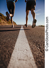 Athletes running on country road - Cropped shot of two...