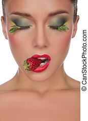 face of young woman with strawberry in mouth