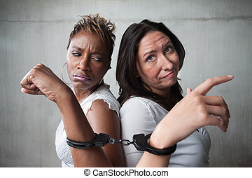Angry women in handcuffs - Two angry women connected by a...