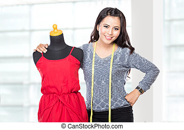 Young asian designer woman posing smiling, hold a scissors,...