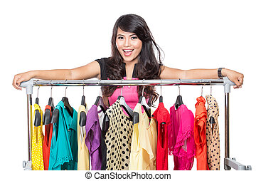 Beautiful woman posing on the rack of clothes in a shop - A...