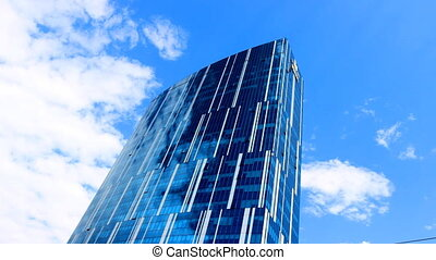 glass wall of a skyscraper - clouds reflected in the glass...