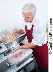 Butcher slicing ham