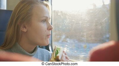 Woman having snack while traveling by train - Young woman...