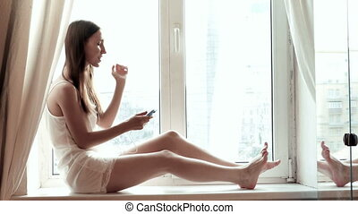 young woman listening music in room near the window