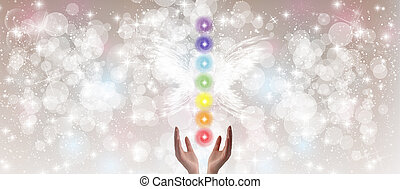 Healing Hands and seven chakras on a sparkling pastel...