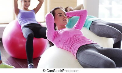 happy women flexing abdominal muscles on fitball - fitness,...