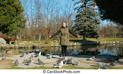 Cheerful Girl Standing In the Park Surrounded With Pigeons -...